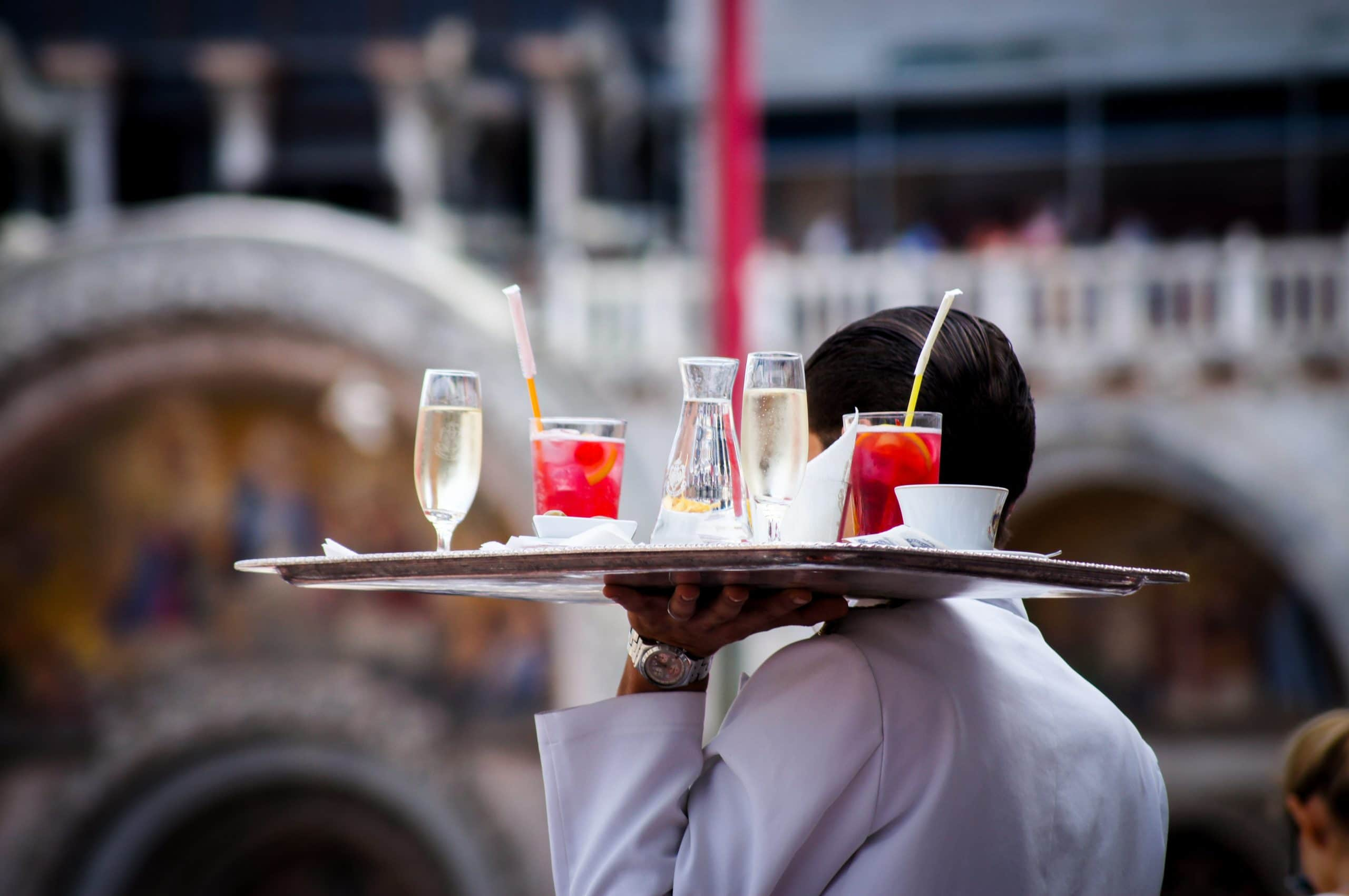 Waiter carrying drinks on tray