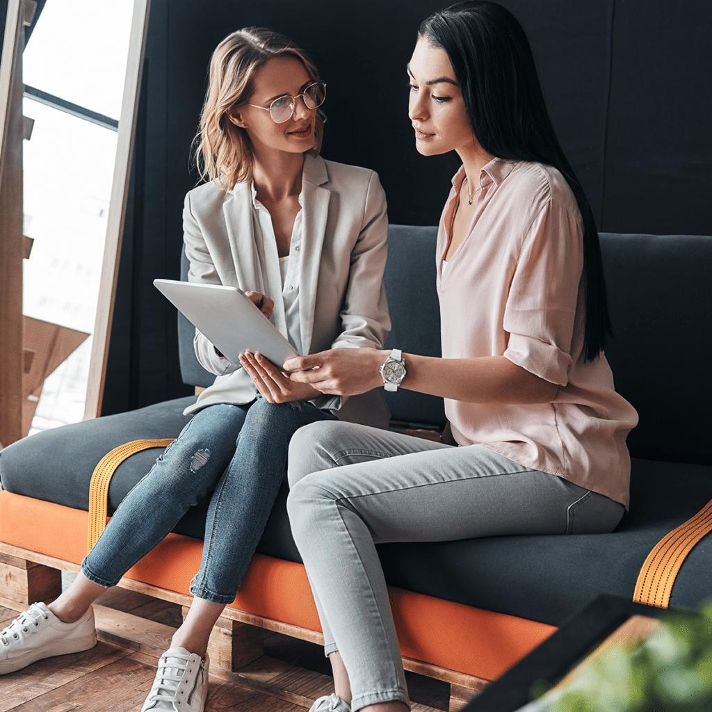 Smiling career women looking at ipad